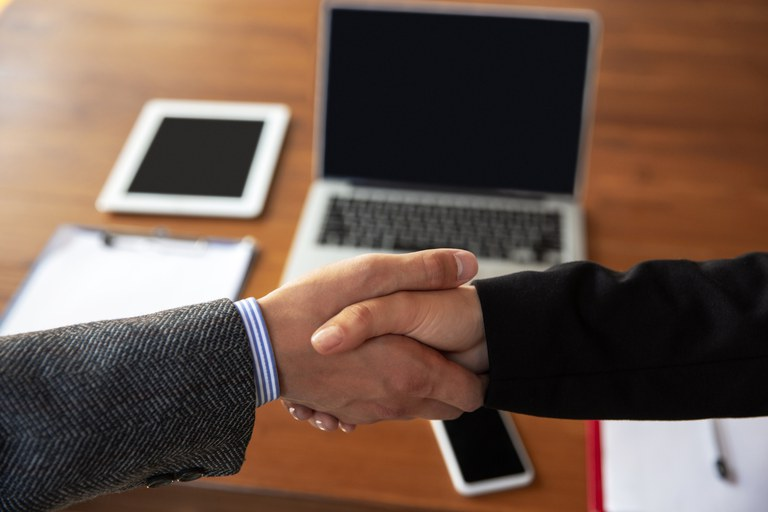 close-up-businessmen-shaking-hands-conference-room.jpg