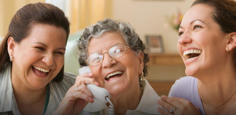 Três mulheres estão alegres ao utilizar o telefone fixo