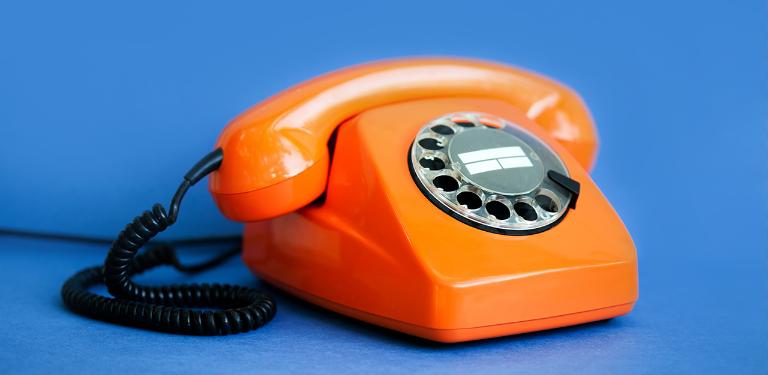 Telefone de disco laranja sobre fundo azul