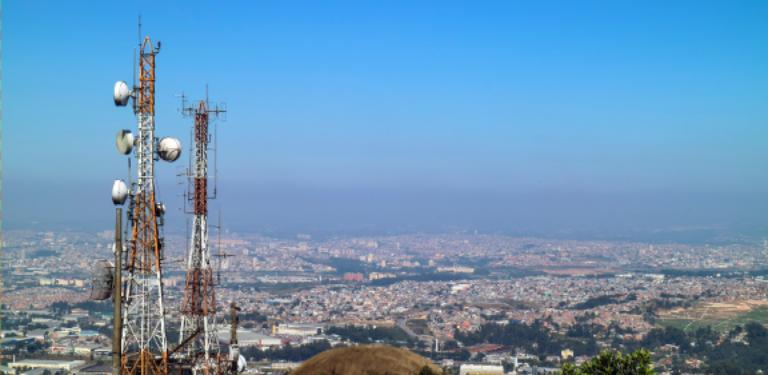 Antena de celular com uma cidade ao fundo