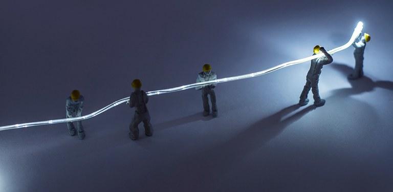 Uma fibra óptica é carregada por personagens que representam trabalhadores