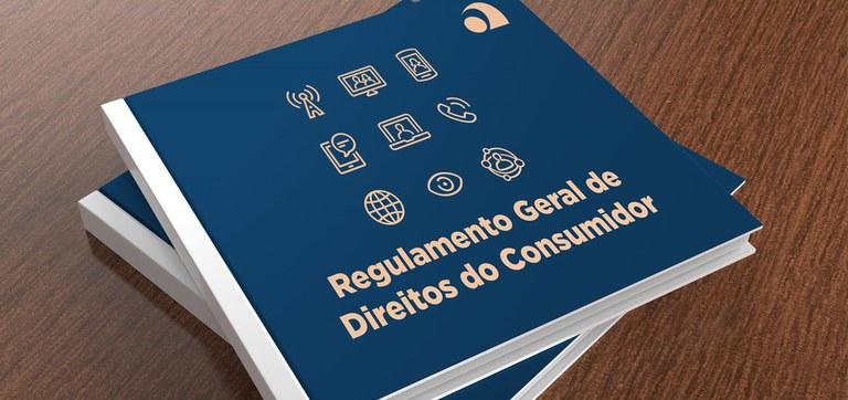 """Dois cadernos azuis intitulados """"Regulamento Geral de Direitos do Consumidor"""" formam uma pilha sobre uma mesa de madeira."""