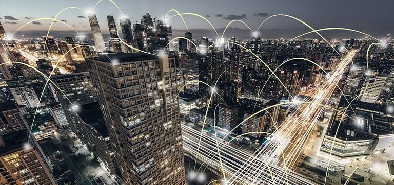 Linhas e retas, representando as vias de telecomunicações, conectam diversos equipamentos em uma cidade