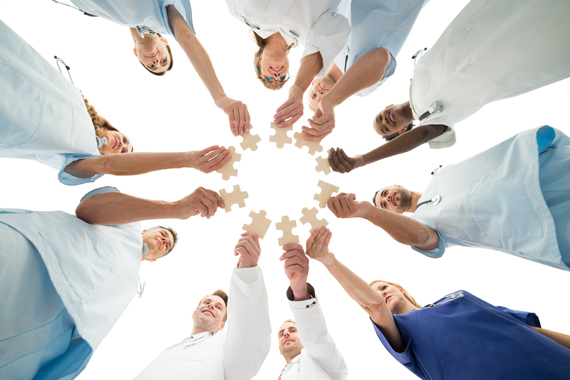 Directly below shot of medical team joining jigsaw pieces in huddle against white background