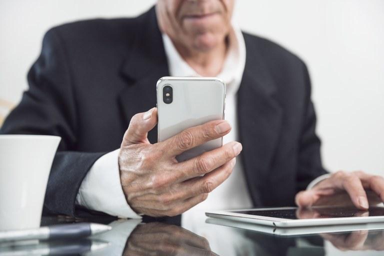 close-up-of-an-elderly-man-holding-smart-phone-in-hand.jpg